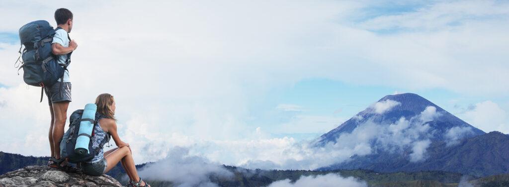 Mann und Frau stehen auf einer Bergspitze und blicken in die Ferne